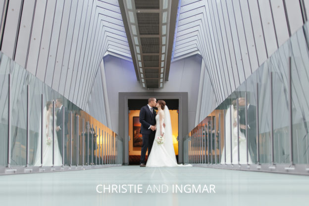 bride and groom kissing on hilton skywalk