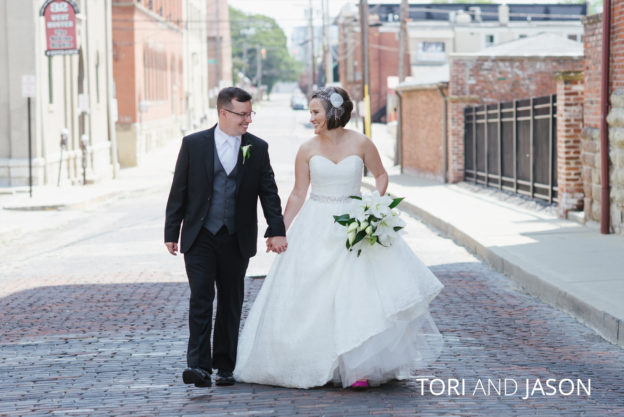 bride and groom walking on a brick road