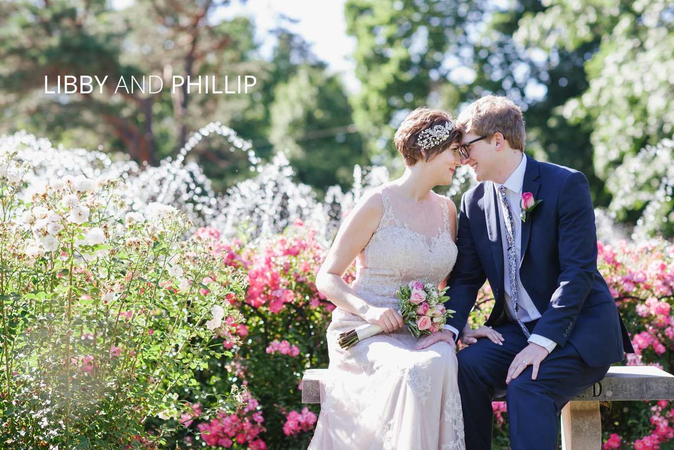 bride and groom in front of fountain surrounded by roses