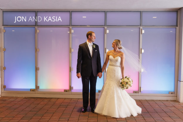 bride and groom holding hands in front of LED lights