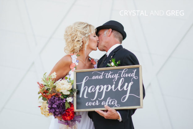 cute couple kissing holding a sign