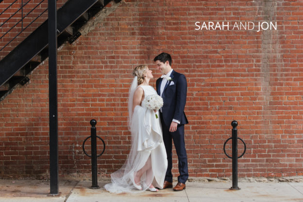 bride and groom in short north columbus against brick wall