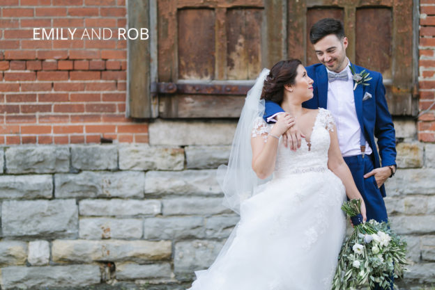 bride and groom smiling at eachother in front of brick wall