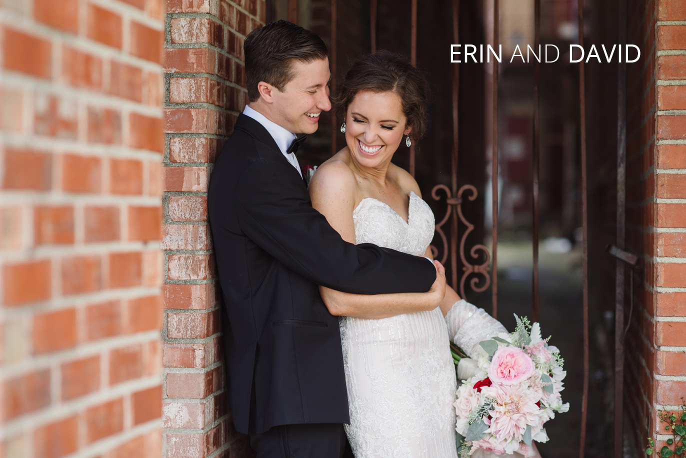 newlyweds hugging against a brick wall