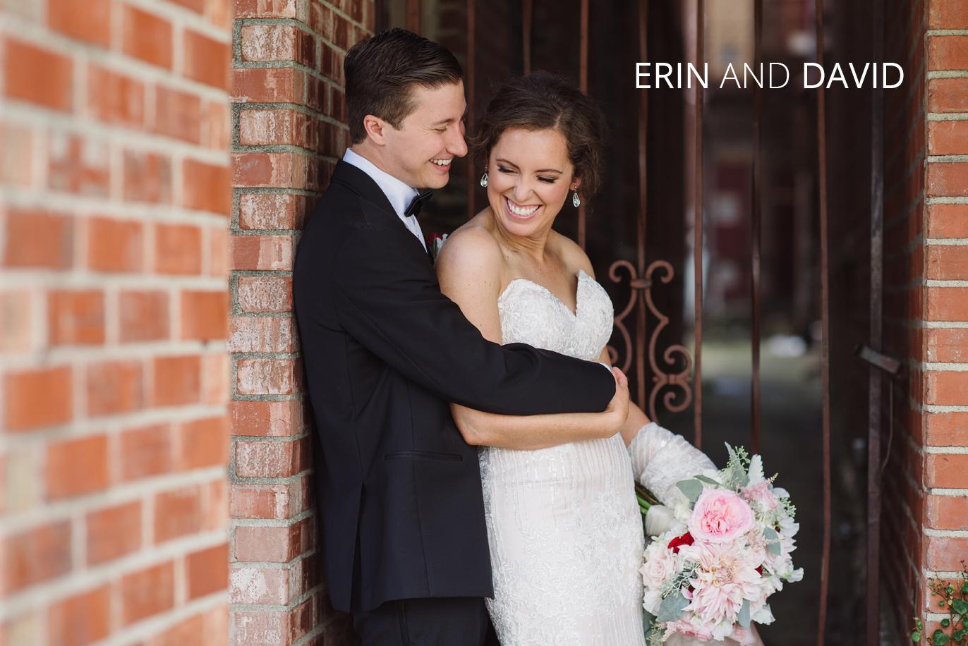 newlyweds hugging against a brick wall
