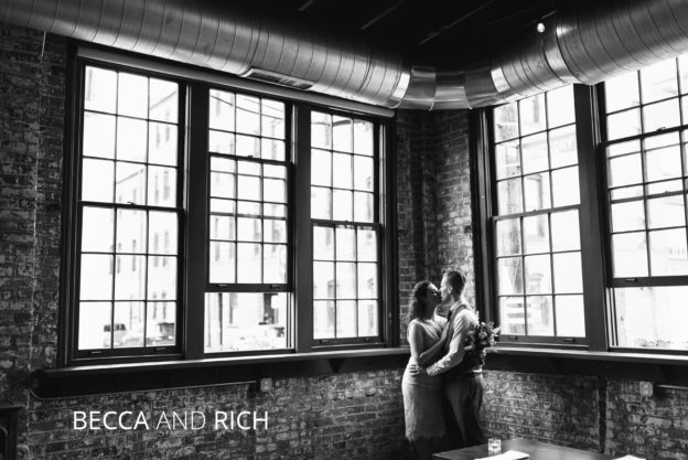 married couple kisses in front of brick wall
