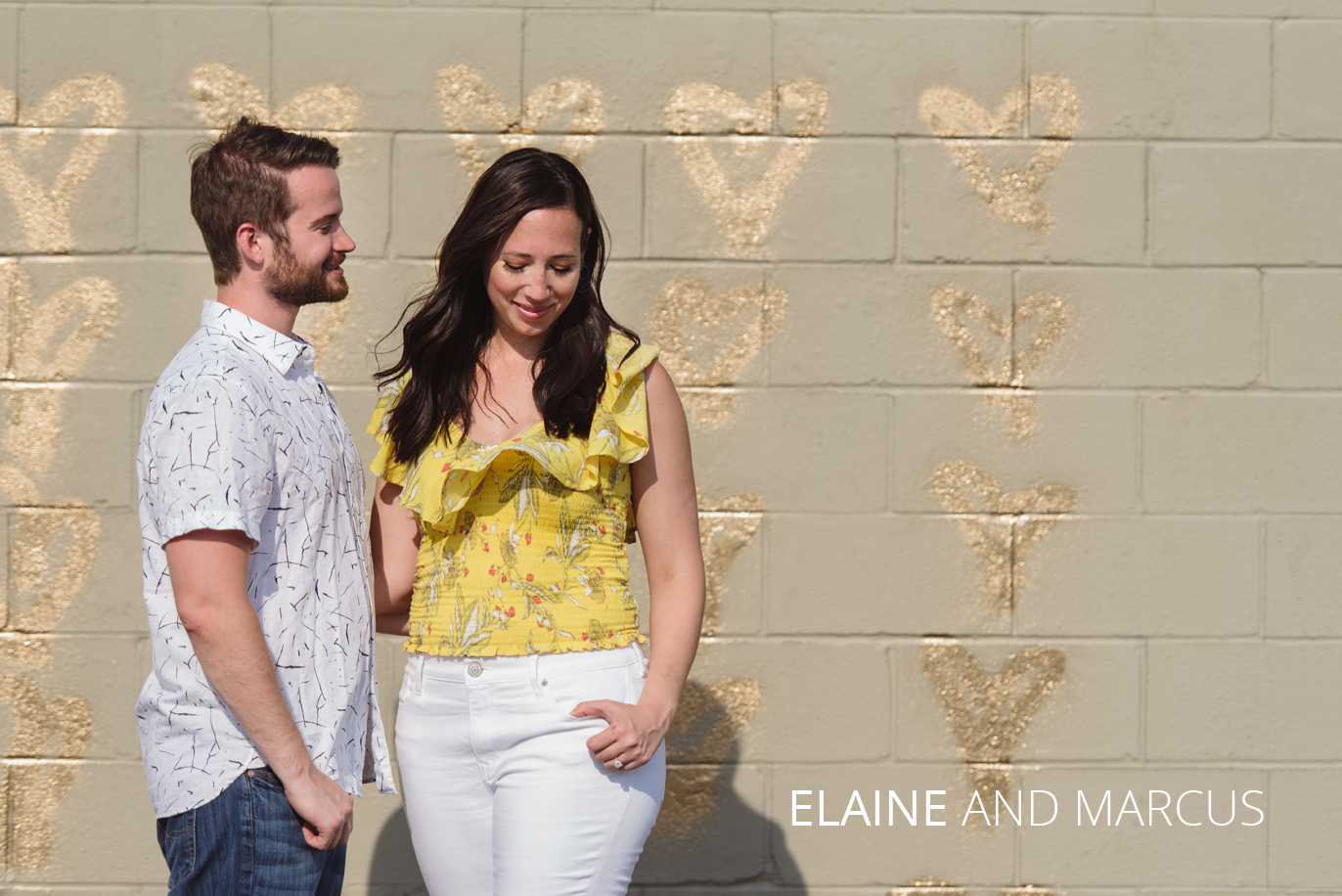 elaine and marcus in front of a wall of hearts