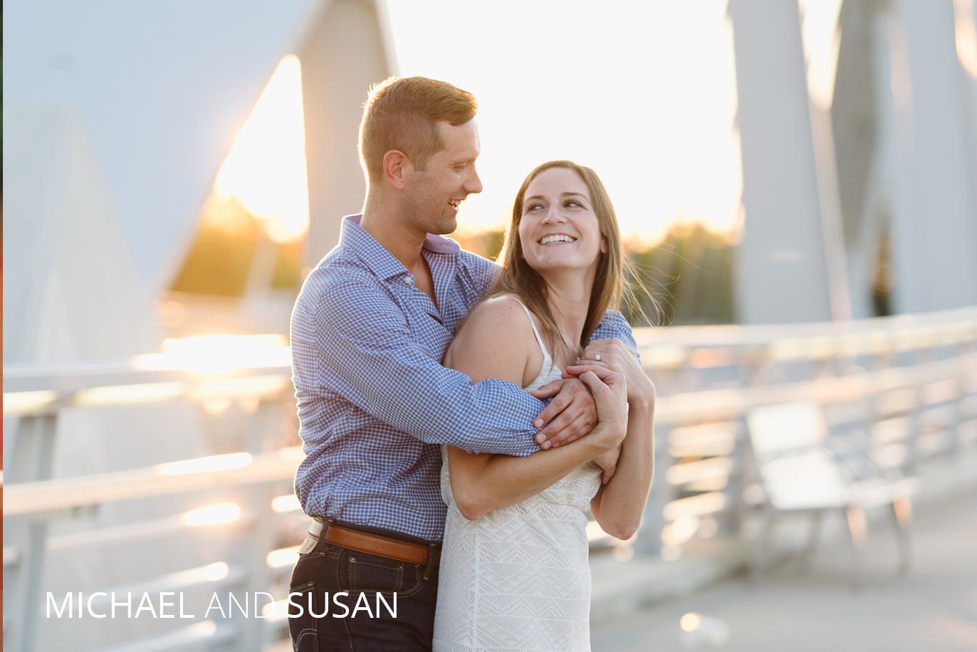 michael and susan hugging on the main street bridge at sunset
