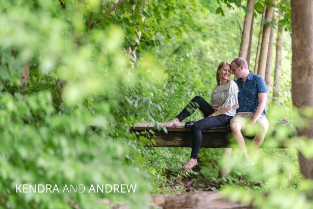 kendra and andrew sitting on a bridge
