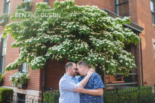 two men hugging under a tree